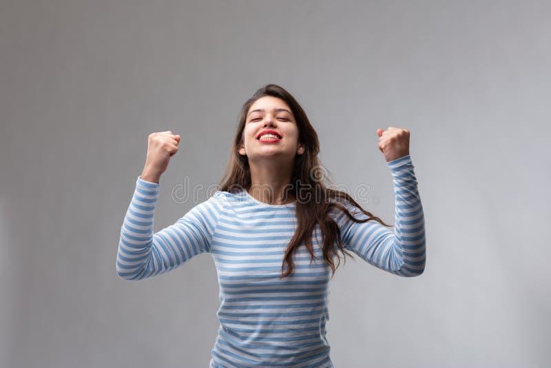 Triumferande fröjd för ung kvinna arkivfoto