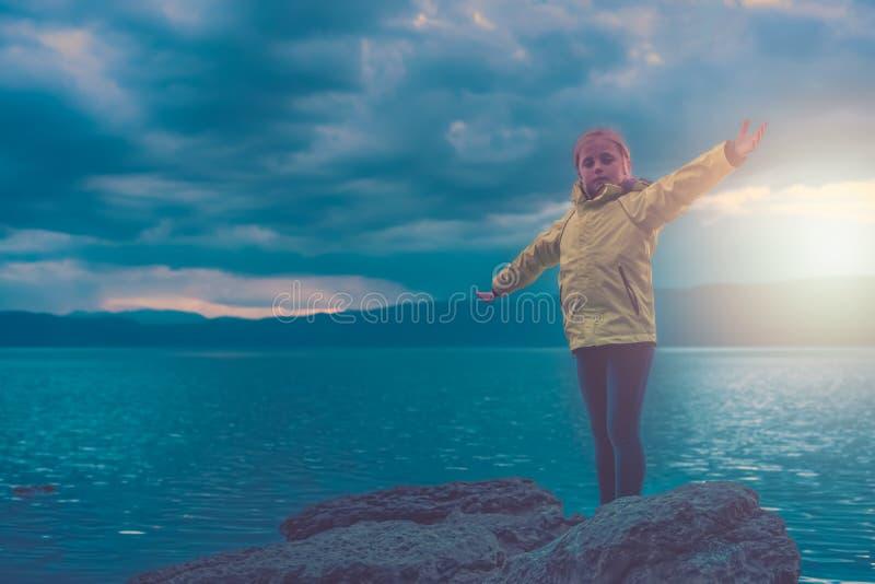 Triumferande liten flicka på sjökust royaltyfri fotografi