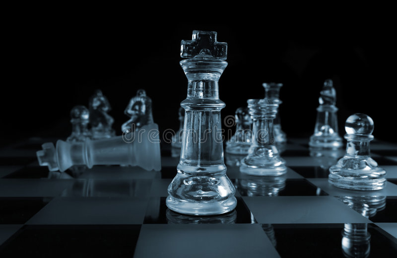 Triumph. Glass Chess Pieces on a Frosted Glass Chess Board stock image