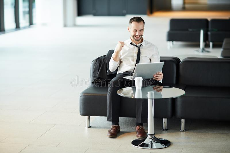 Triumph. Successful businessman in formalwear expressing triumph while sitting in airport lounge with laptop in front royalty free stock photos