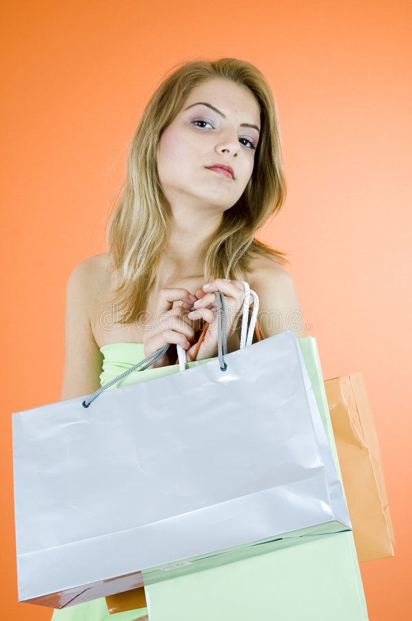 Triumphant Bargain Hunter. Woman holding shopping bags with a triumphant expression stock photos