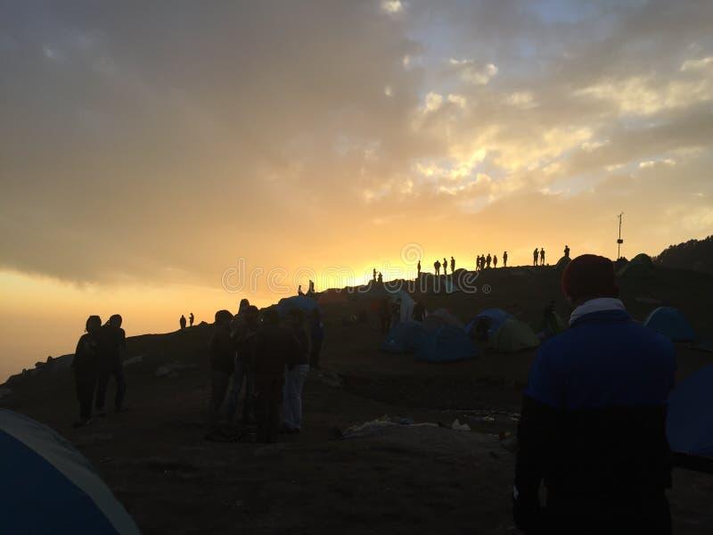 Triund野营的人围拢的日落视图 库存照片