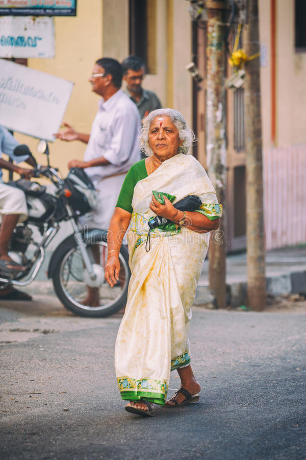 Trivandrum, India - February 17, 2016: old woman in sari walks in the street. Wearing traditional sari. Saris are wrapped around the body, 4 to 8 metres in royalty free stock photography