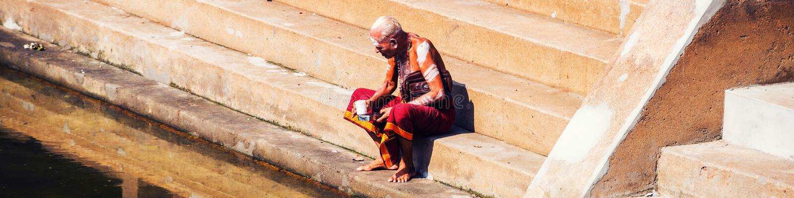 Old man wearing typical robe siting at Sree Padmanabhaswamy Temple pool during the sunny day in Trivandrum, India. TRIVANDRUM, INDIA - MAY 15, 2016: Old man royalty free stock photo