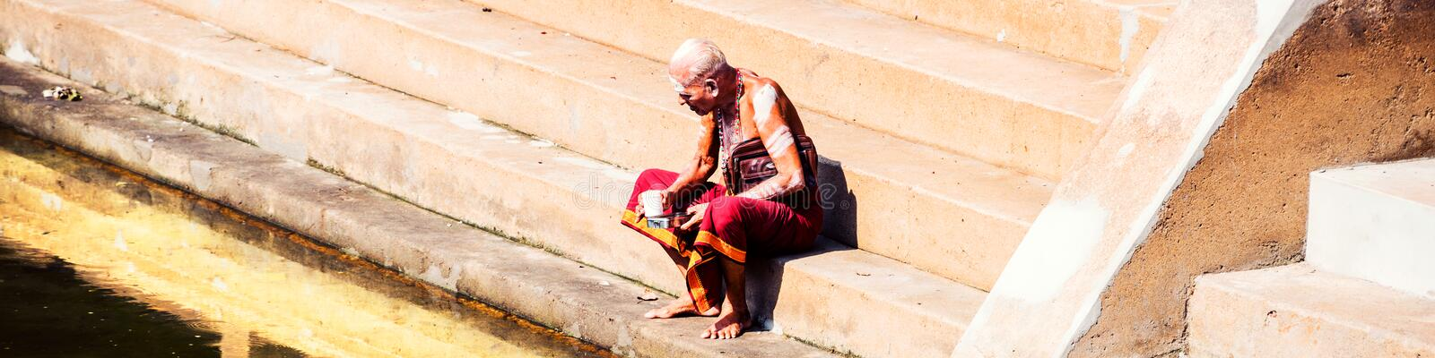 Old man wearing typical robe siting at Sree Padmanabhaswamy Temple pool during the sunny day in Trivandrum, India. TRIVANDRUM, INDIA - MAY 15, 2016: Old man royalty free stock image