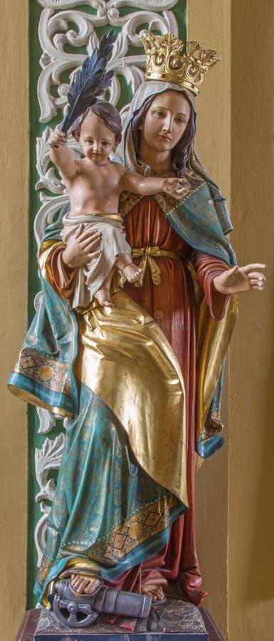 Trnava -玛丹娜被雕刻的雕象和平的在从19的阴险的人教会里 分 免版税库存图片
