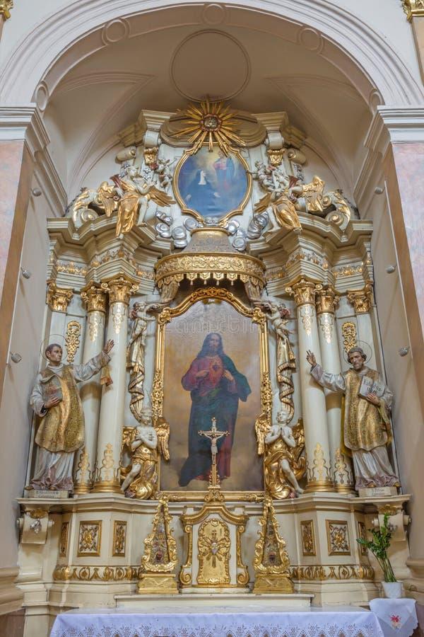TRNAVA, SLOVAQUIE - 3 MARS 2014 : L'autel baroque latéral dans l'église de jésuites de 18 cent photo libre de droits