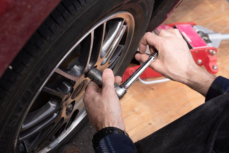 Trocando as rodas e os pneus do inverno ao verão em seu carro Barra da ruptura e jaque do carro que está sendo usado imagens de stock royalty free