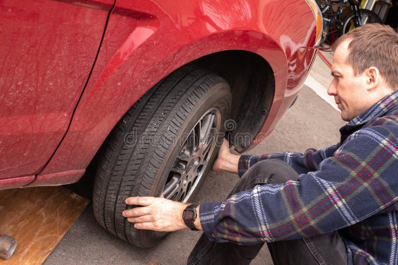 Trocando as rodas e os pneus do inverno ao ver?o em seu carro Barra da ruptura e jaque do carro que est? sendo usado imagens de stock