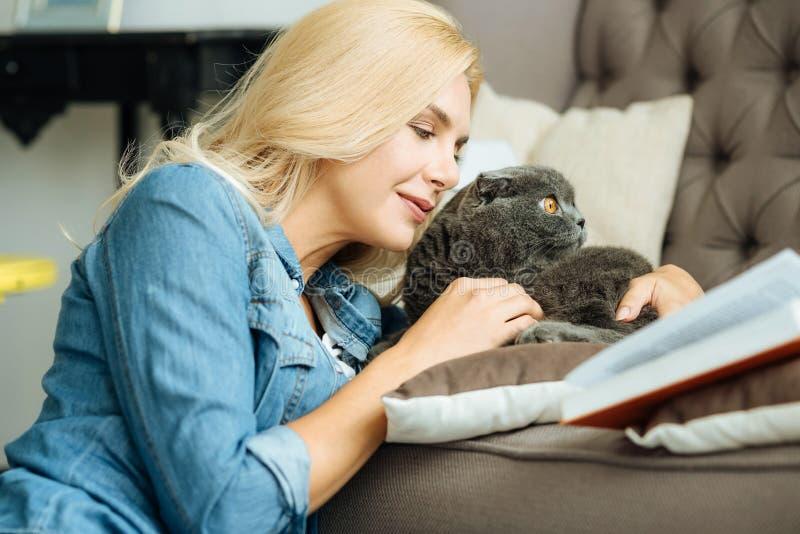 Trocas de carícias bonitas da mulher seu gato imagem de stock royalty free