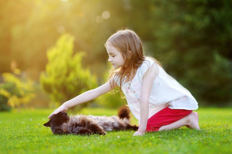 Trocas de carícias bonitos da menina um gato preto gigante imagens de stock