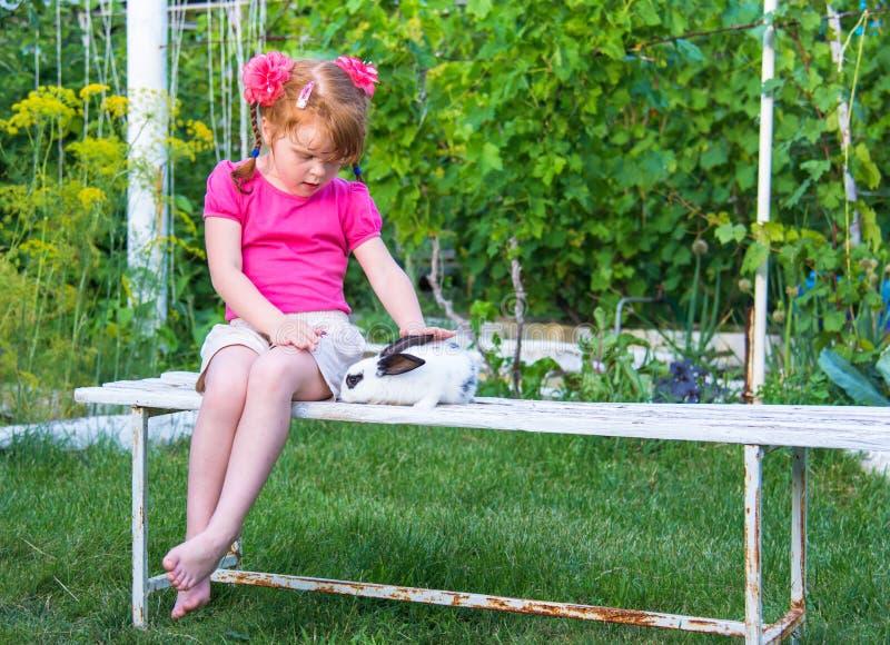 Trocas de carícias da menina um coelho em um banco imagem de stock royalty free
