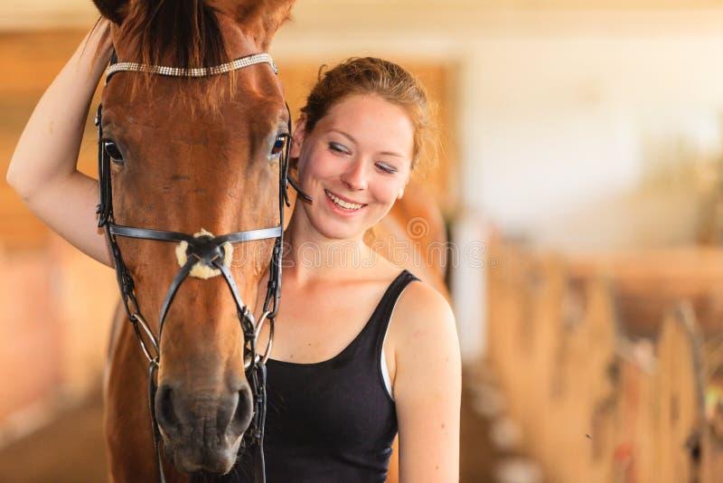 Trocas de carícias da moça do jóquei e aperto do cavalo marrom fotos de stock