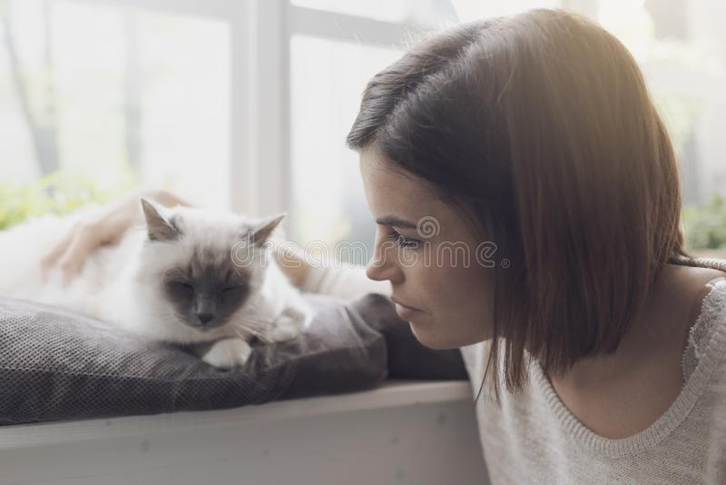 Trocas de carícias da mulher seu gato ao lado de uma janela foto de stock royalty free