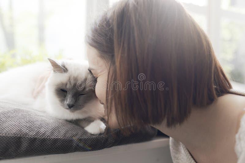 Trocas de carícias da mulher seu gato ao lado de uma janela imagens de stock royalty free