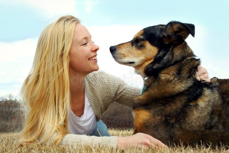 Trocas de carícias da mulher seu pastor alemão Dog Outside fotografia de stock royalty free