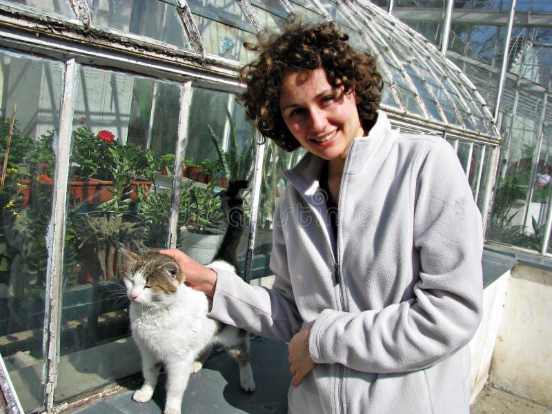 Trocas de carícias felizes da mulher um gato fotos de stock
