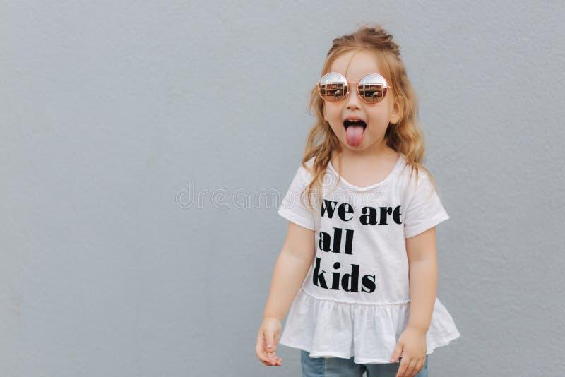 Trochę girldressed w białej koszula z tekstem, jesteśmy wszystkie dzieciakami zdjęcie stock