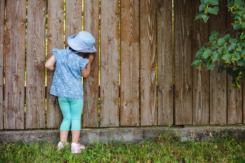 Trochę wtrącać się dzieciaka błyska od dziury w ogrodzeniu w świacie na zewnątrz swój podwórka fotografia stock