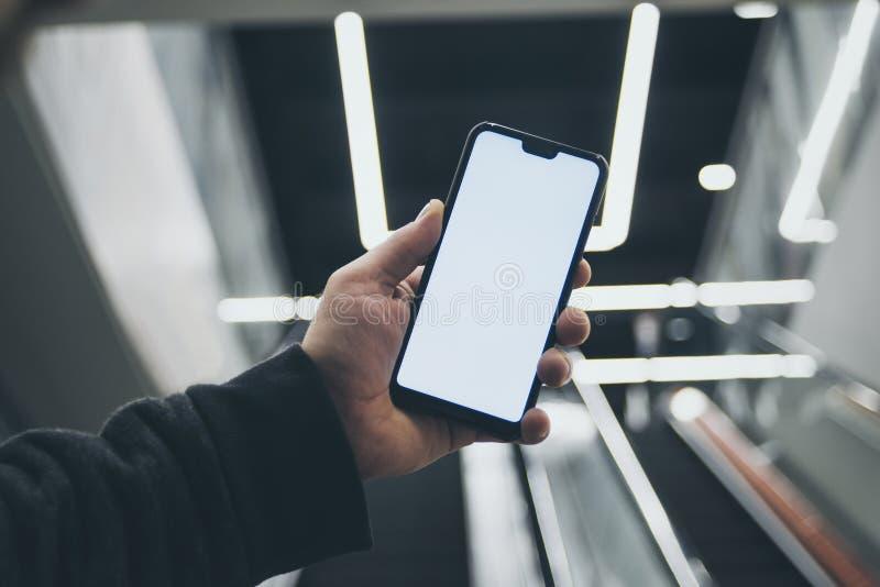 Trocista acima de um smartphone à disposição, no fundo de uma escada rolante em um shopping e em umas lâmpadas luminosas imagens de stock royalty free