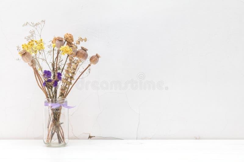 Trockenblumen und Mohnblume geht in einem Glasgefäß auf weißem gebrochenem wa voran stockfotografie