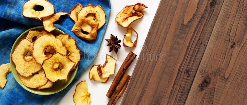 Trockene Apfelchips und -gewürze auf weißem und braunem hölzernem Hintergrund Selbst gemachte gebackene geschnittene Früchte, ges stockbild