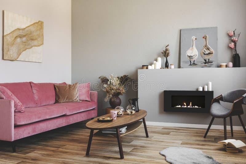 Trockene Blumen im Tonwarenvase auf kleinem Holztisch nahe bei rosa Couch des Samts im grauen Wohnzimmer lizenzfreies stockbild