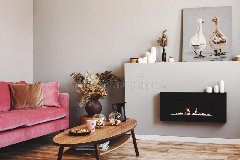 Trockene Blumen im Tonwarenvase auf kleinem Holztisch nahe bei rosa Couch des Samts im grauen Wohnzimmer stockbilder
