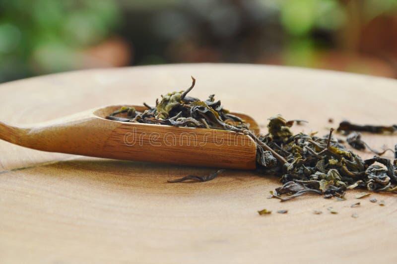Trockene chinesische Teeblätter in der Schaufel auf Hiebblock lizenzfreie stockbilder