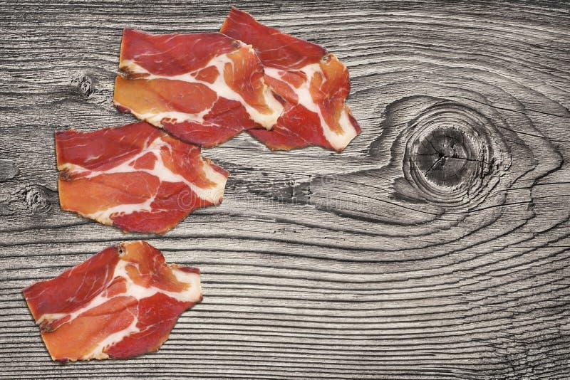 Trockene kurierte Schweinefleisch-Hals-Scheiben eingestellt auf alten geknoteten verwitterten hölzernen Picknicktisch stockbilder