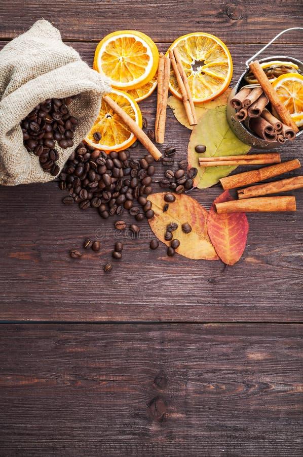 Trockene Orange und Zitrone, Kaffeebohnen in der Tasche, Zimt und gefallener Herbstlaub stockfotos