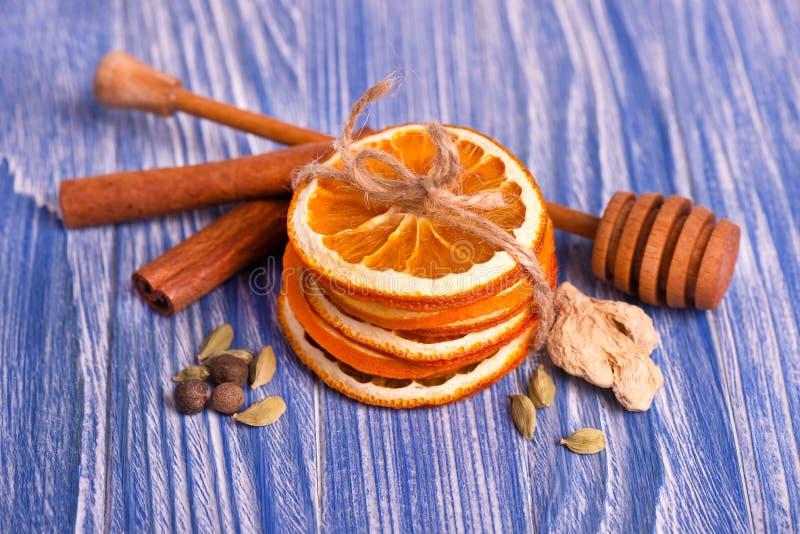Trockene Scheiben der Orange, des Zimts, des Ingwers und des Kardamoms, auf einem blauen hölzernen Hintergrund Aromatische Gewürz lizenzfreie stockfotografie