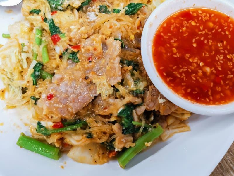 Trockene Suki Thai Style mit Chinakohl, Schweinefleisch, Suppennudeln und Sellerie auf einer weißen Platte, Straßennahrung stockfotos