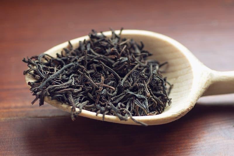 Trockene Teeblätter im hölzernen Löffel auf braunem Hintergrundnahaufnahmemakro stockfoto