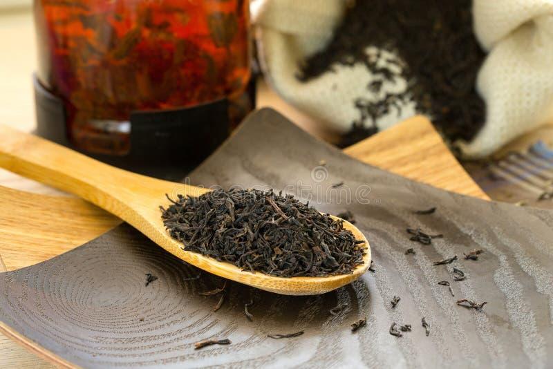Trockener schwarzer Tee auf einem hölzernen Löffel lizenzfreie stockbilder