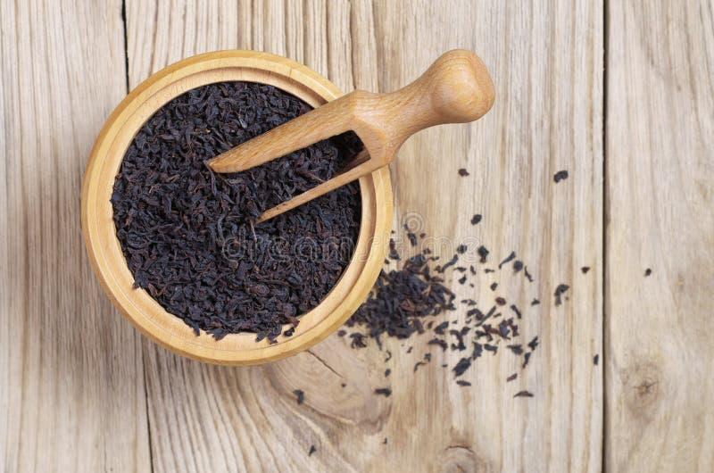 Trockener schwarzer Tee in der Schüssel mit Löffel stockfoto
