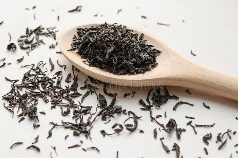 Trockener schwarzer Tee im hölzernen Löffel lizenzfreie stockfotografie