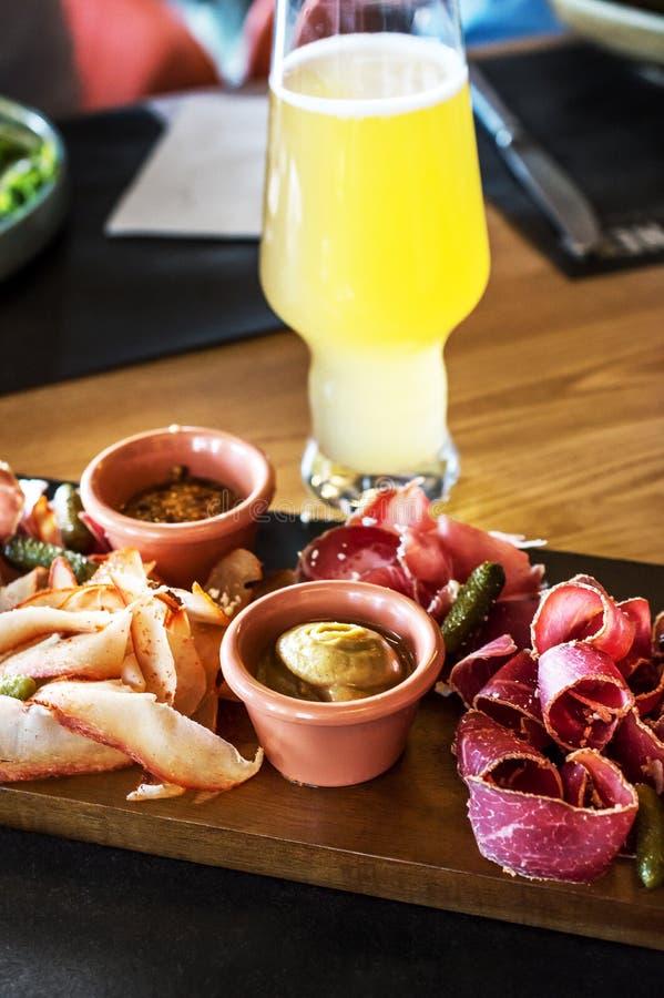Trockenfleisch mit Glas Bier auf dem Tisch stockbild