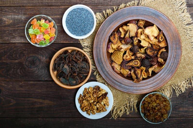 Trockenfrüchteäpfel, Birnen, Aprikose, Beeren, Walnusskerne, Rosinen, Mohn in einer Schüssel auf dunklem hölzernem Hintergrund lizenzfreie stockbilder