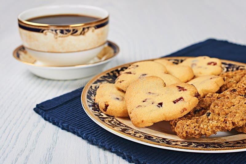 Trocknen-Moosbeerkeks-Herzen und Hafermehl-Rosinen-Plätzchen mit Kaffee stockfotos