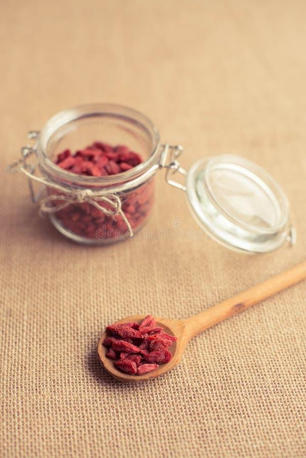 Trocknen Sie rote goji Beeren im hölzernen Löffel auf rustikalem Hintergrund für eine gesunde Diät stockfotos