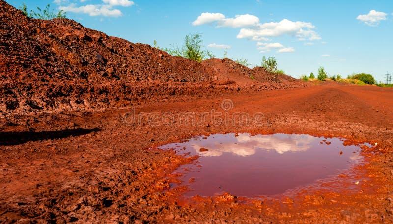 Trocknen Sie roten Boden mit Pfütze in Kryvyi Rih, Ukraine stockfotos