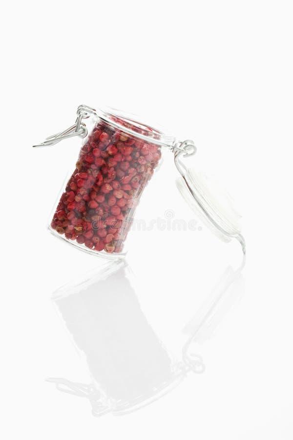 Trocknen Sie roten Pfeffer im Glasgefäß auf weißem Hintergrund stockfoto