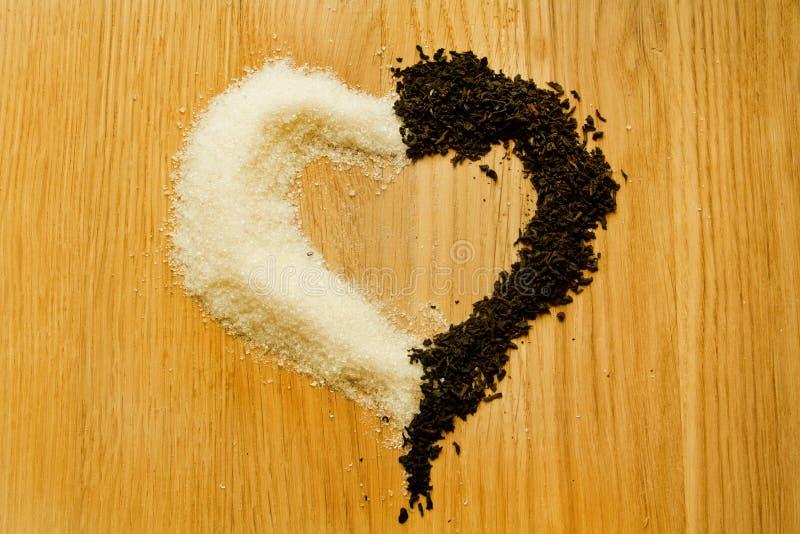 Trocknen Sie schwarzen Tee und Zucker in Form eines Herzens stockbild