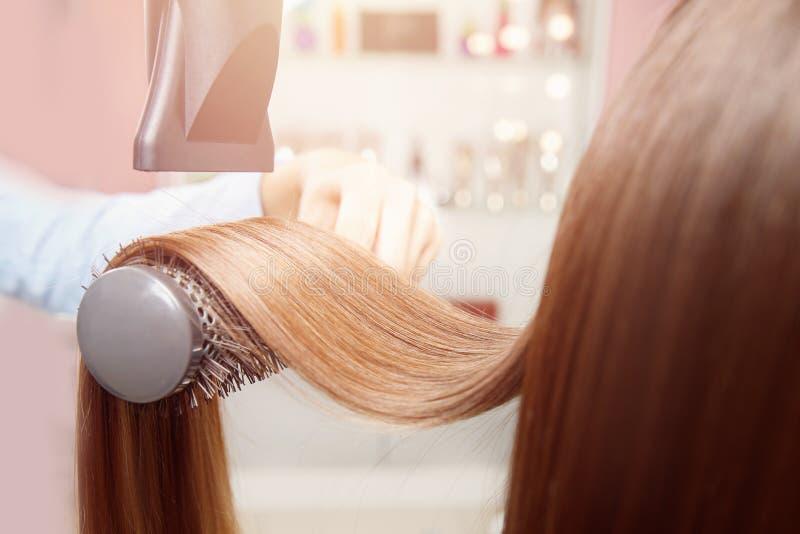 Trocknend und glänzende Stränge des Trockners der dunkelbraunen Haarnahaufnahme anredend stockbilder
