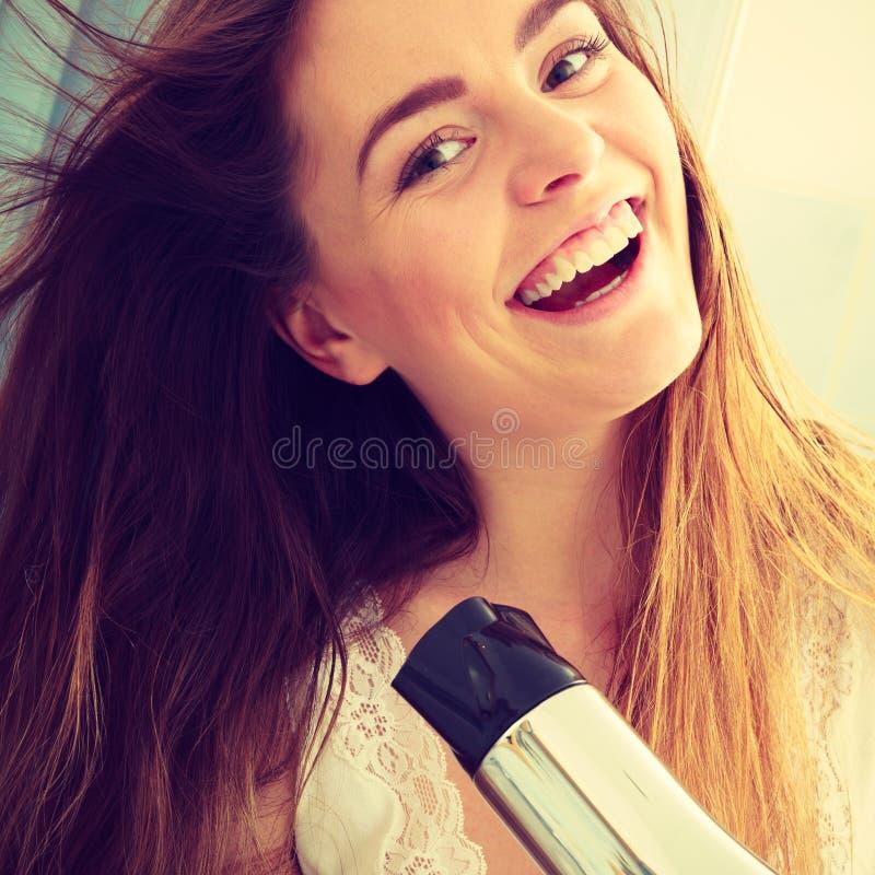 Trocknendes Haar der langhaarigen Frau im Badezimmer haircare lizenzfreie stockbilder