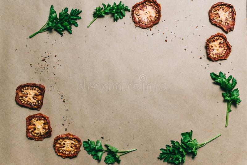 Trocknete frische Petersilie der Tomaten mit Gewürzen auf Papier lizenzfreie stockbilder