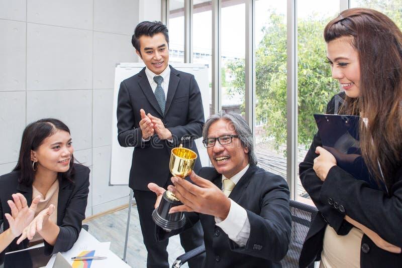 Troféu de vencimento da equipe do negócio no escritório Homem de negócios com te imagens de stock royalty free
