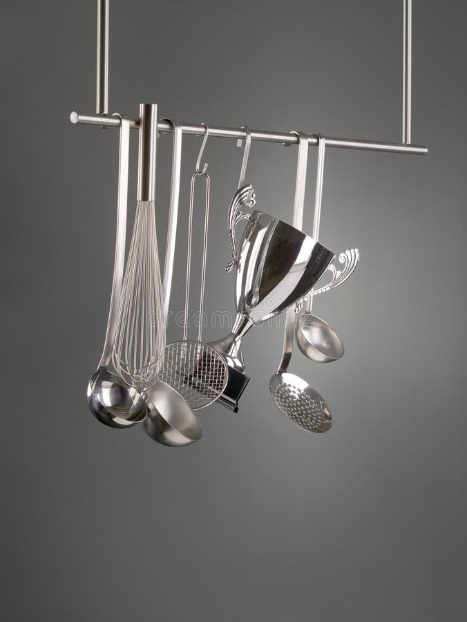 Troféu do copo entre utensílios da cozinha imagens de stock