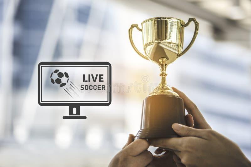 Troféu dourado do campeão para o fundo do vencedor com sc vivo do futebol fotos de stock
